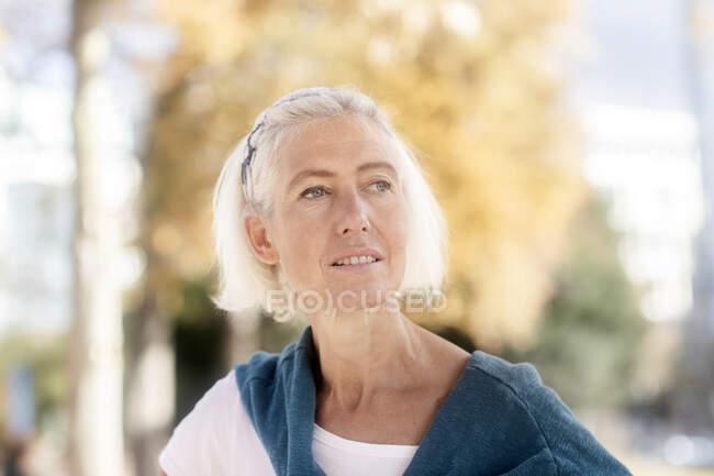 Retrato de la mujer mayor de pie en el parque - foto de stock