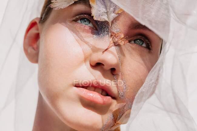 Концептуальный портрет женщины в вуали с высушенными цветами на лице и шее — стоковое фото