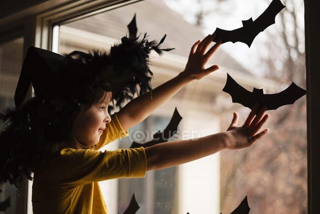 Chica sonriente con un sombrero de brujas pegando decoraciones de murciélagos en una ventana, Estados Unidos - foto de stock