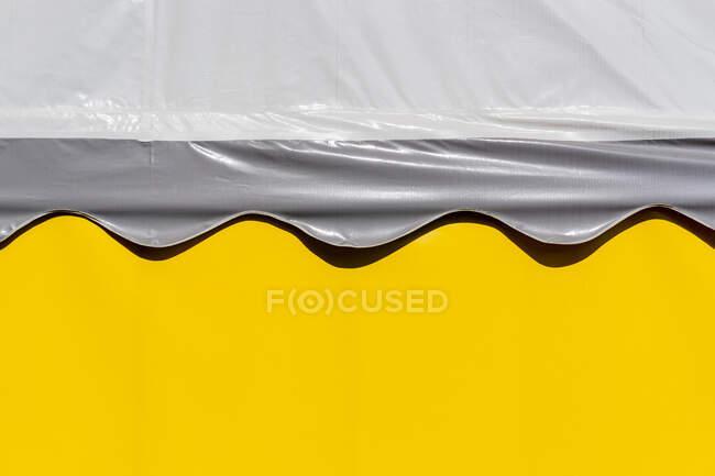 Primer plano de una cubierta de techo de carpa de plástico en una pared amarilla - foto de stock