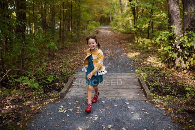 Дівчинка перебігає невеличкий міст на стежці лісу (США). — стокове фото