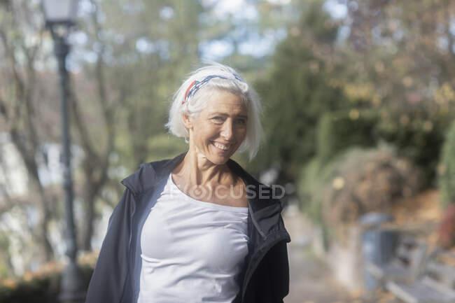 Retrato de la mujer mayor sonriente de pie en el parque - foto de stock