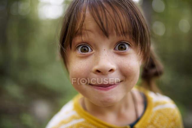 Retrato de una chica con pecas de pie en el bosque tirando caras raras, Estados Unidos - foto de stock