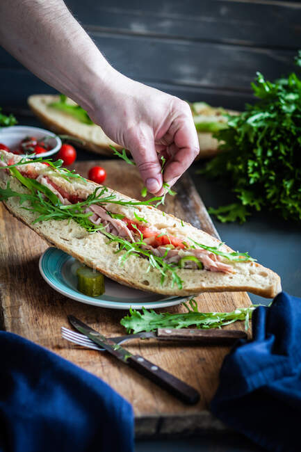 Person preparing a ham, tomato and rocket sandwich with a gherkin — Stock Photo