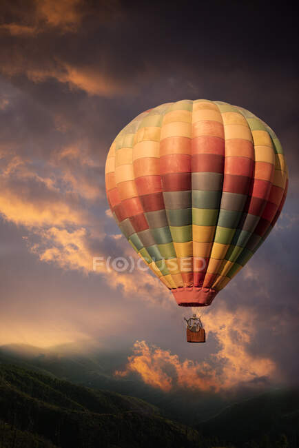 Rabbit and deer in a multi coloured hot air balloon rising above hills towards a stormy sky — Stock Photo