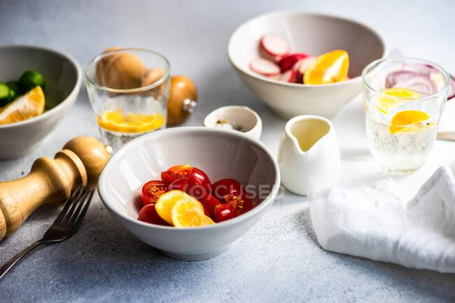 Vaso de agua de limón con tazones de tomate, cebolla roja, rábanos y pepino - foto de stock