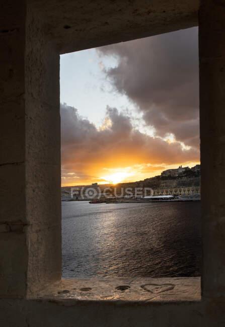 Vista della città vecchia sul Mar Mediterraneo sotto il cielo del tramonto vista attraverso la finestra — Foto stock