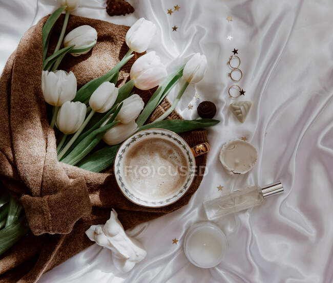 Tazza di caffè con tulipani e gioielli sul tavolo, vista da vicino, concetto di mattina sposa — Foto stock