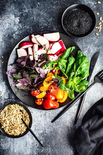 Concepto de comida saludable con verduras crudas y hierbas en plato de cerámica negra con semillas sobre fondo de piedra oscura - foto de stock