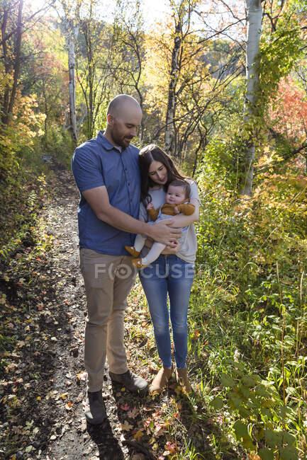 Retrato de una feliz pareja de pie en el bosque con su hija pequeña, California, EE.UU. - foto de stock