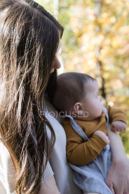Retrato de una mujer de pie en el bosque sosteniendo a su hija pequeña, California, EE.UU. - foto de stock