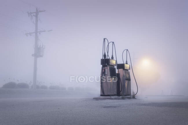 Old fashioned gas pumps on a foggy street at dawn, Australia — Stock Photo