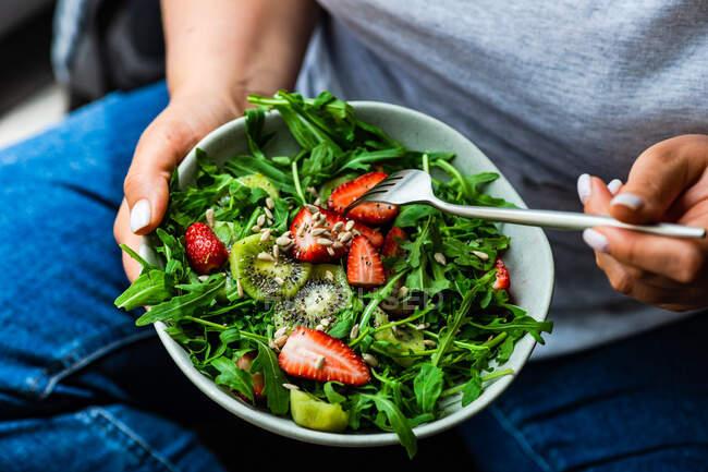Mujer come ensalada de rúcula saludable con fresas y kiwi - foto de stock