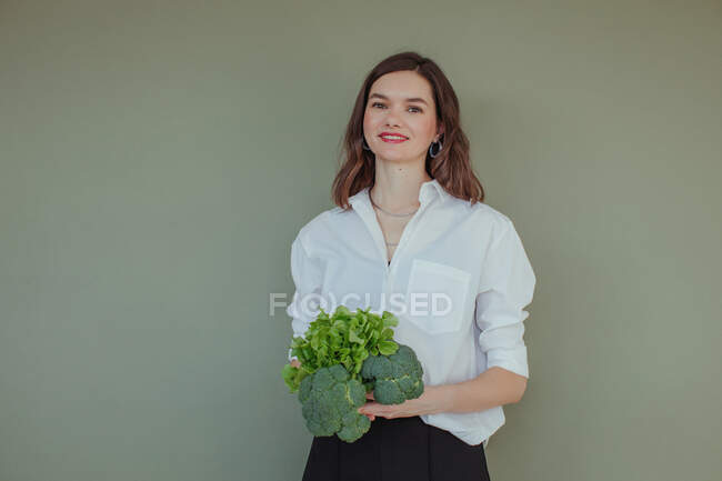 Portrait of a beautiful smiling woman holding fresh broccoli and lettuce — Stock Photo