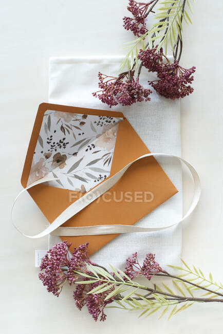 Floral lined envelope with ribbon and fresh flowers — Stock Photo