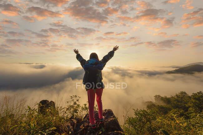 Silueta de una mujer de pie en una montaña sobre la alfombra de nubes, Tailandia - foto de stock