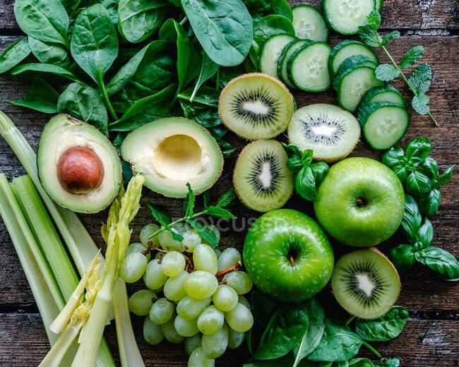 Vista aérea de frutas y verduras verdes frescas sobre una mesa de madera - foto de stock