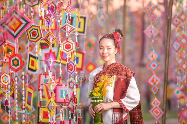 Retrato de uma mulher sorridente em roupas tradicionais tailandesas segurando flores, Tailândia — Fotografia de Stock