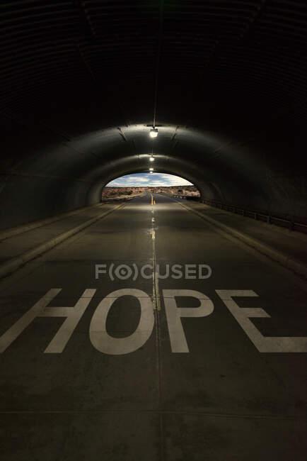 Слово надія, записане на дорозі з світлом в кінці тунелю, уза — стокове фото