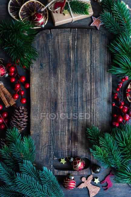 Palline di Natale, decorazioni e rami di abete accanto al tagliere di legno — Foto stock