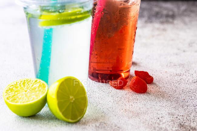 Limonada de fresa y lima con limonada de menta sobre una mesa con cubitos de hielo, lima fresca y fresas - foto de stock