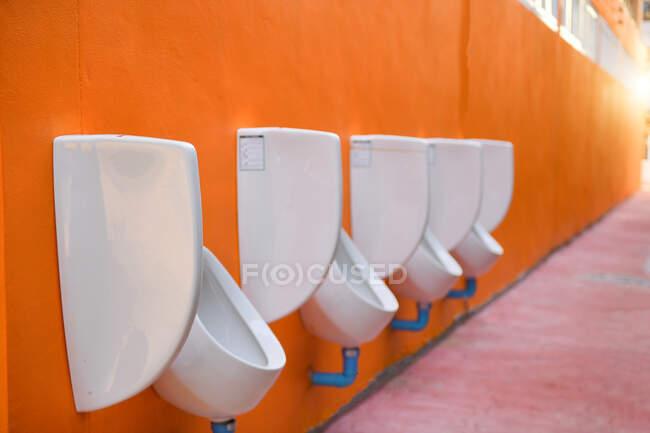 Fila de urinarios públicos colgando de una pared naranja - foto de stock