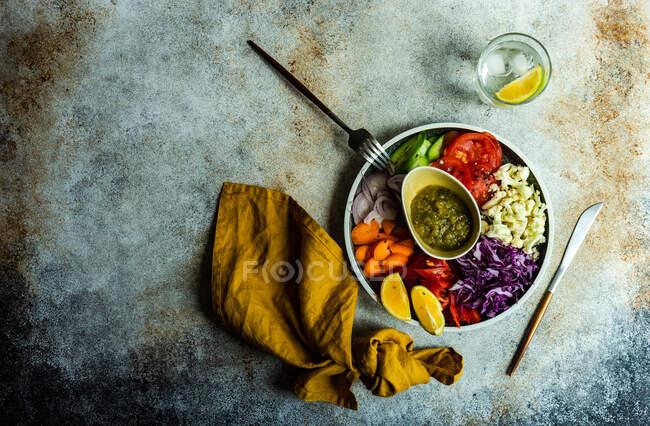 Cena saludable con verdura orgánica servida sobre una mesa con semillas de sésamo y un vaso de agua de limón - foto de stock