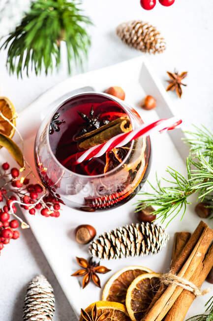 Concepto de bebida navideña con copa de vino caliente con especias alrededor - foto de stock