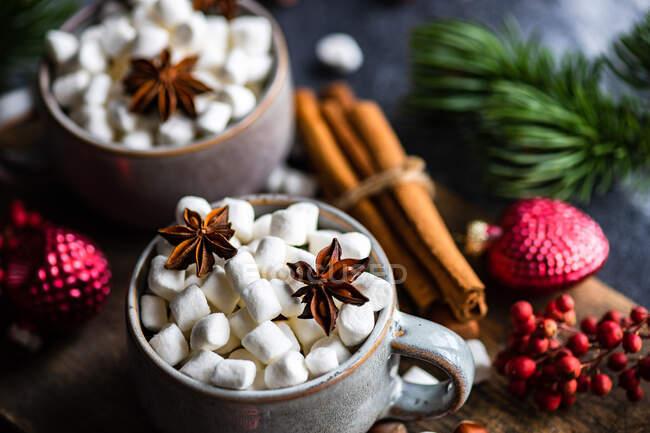 Tazas llenas de mini malvaviscos con especias sobre fondo oscuro como concepto de comida navideña - foto de stock