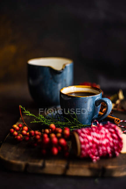 Café con especias navideñas en taza de cerámica azul entre especias y bayas sobre fondo oscuro y malhumorado - foto de stock