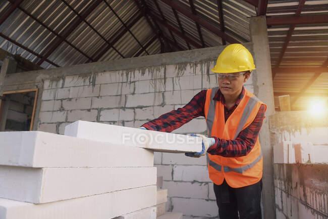 Constructor albañil tendiendo ladrillos y construyendo barbacoa en sitio industrial - foto de stock
