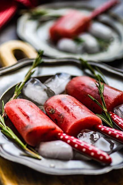 Postre de verano con paletas de sandía orgánicas servidas en plato con hielo y romero - foto de stock