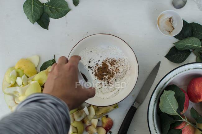 Mano humana derramando canela en plato - foto de stock
