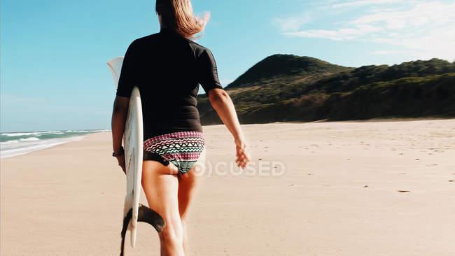 Menina com prancha de surf na praia — Fotografia de Stock