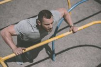 Overhead view of handsome sportsman doing push up at horizontal bar — Stock Photo
