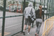 Rear view of sportive couple walking to sports ground — Stock Photo