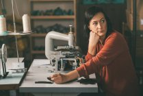 Mature thoughtful seamstress sitting at workplace in tailor shop — Stock Photo