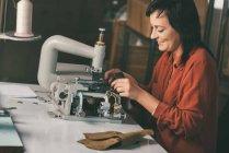 Sonriente costurera madura de cuero en la máquina eléctrica - foto de stock