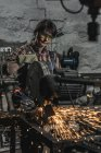 Female welder in protective googles using welding torch in workshop — Stock Photo