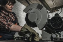 Concentrated female welder using welding torch in workshop — Stock Photo