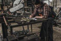 Женщина-сварщик делает бумажную работу за столом в мастерской — стоковое фото