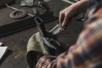 Partial view of welder working on peace of metal in workshop — Stock Photo