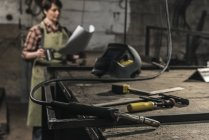 Selective focus of welder with cup of hot drink reading papers in workshop — Stock Photo