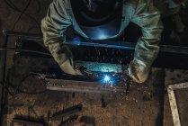 Overhead view of welder in protective work wear holding welding torch in workshop — Stock Photo