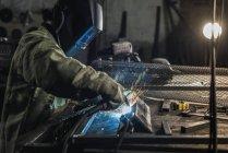 Вид збоку зварювальником в захисних робочий одяг роботи з в майстерні факел зварювання — стокове фото