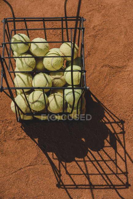 High angle view of basket of tennis balls standing on court — Stock Photo