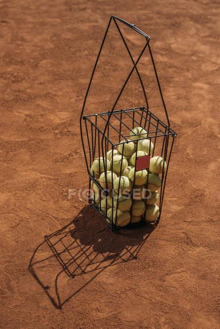 Basket of tennis balls standing on orange court surface — Stock Photo