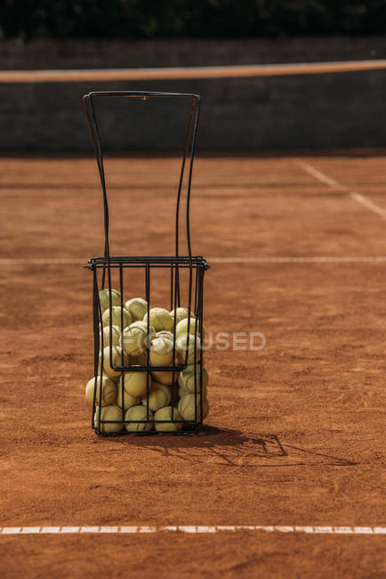 Cesta de pelotas de tenis en cancha - foto de stock