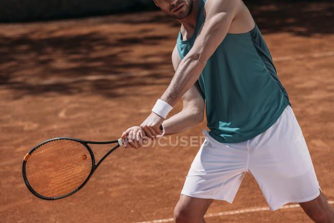 Обрезанный кадр теннисиста делает хит с ракеткой — стоковое фото
