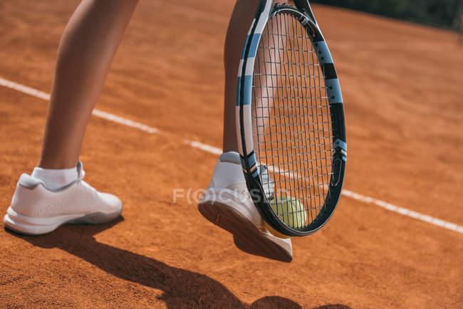 Schnappschuss von Frau, die Tennisball mit Schläger und Bein aufhebt — Stockfoto